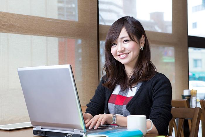 パソコンを見て笑っている女性